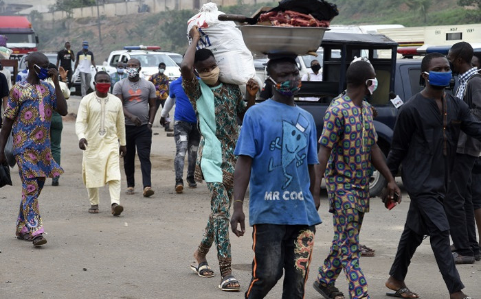 FILE: People wear face masks ahead police checkpoint in compliance with state directive to curb the spread of COVID-19 at Ojodu-Berger in Lagos, on 4 May 2020. Picture: AFP.