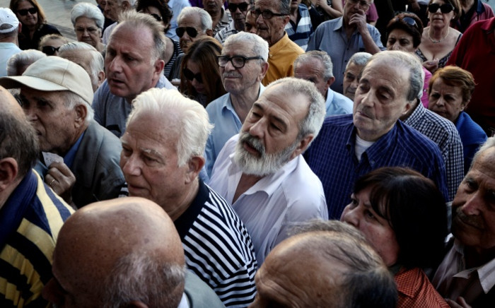 Pensioners wait to get their pensions outside a National Bank of Greece branch in central Athens on 2 July 2015, as banks only opened for pensioners to allow them to get their pensions, with a limit of €120. Picture: AFP.