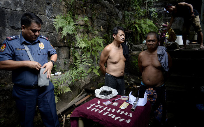 FILE: Two alleged drug dealers stand next to drug paraphernalia confiscated during a police operation conducted in Manila on 15 March 2018. Picture: AFP