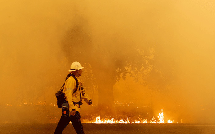 A Pacific Gas and Electric firefighter walks down a road as flames approach in Fairfield, California during the LNU Lightning Complex fire on 19 August 2020.  Picture: AFP