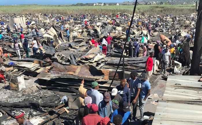 Masiphumelele residents sifting through debris following last night's blaze that destroyed around 1,000 homes. Picture: Kevin Brandt/EWN