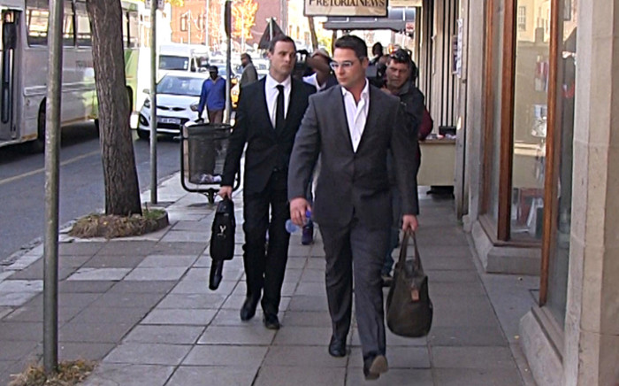 Oscar Pistorius is accompanied by his brother Carl as they head to the High Court chambers in Pretoria following day 38 of the athlete's murder trial. Picture: Reinart Toerien/EWN.