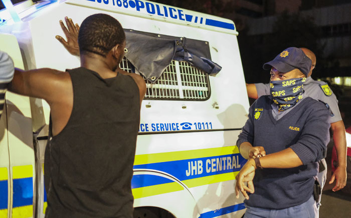 A South African Police Service (SAPS) officer gestures towards his watch while asking a pedestrian why he is not home before the new curfew time, to help curb the spread of COVID-19, in Johannesburg on 29 December 2020. Picture: AFP