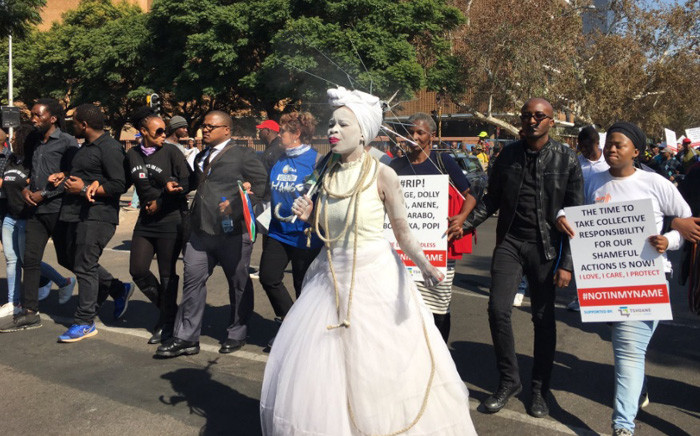 A woman in a piece of performance art leads hundreds marching to Union Buildings in Pretoria calling for an end to women abuse. Picture: Katleho Sekhotho/EWN.