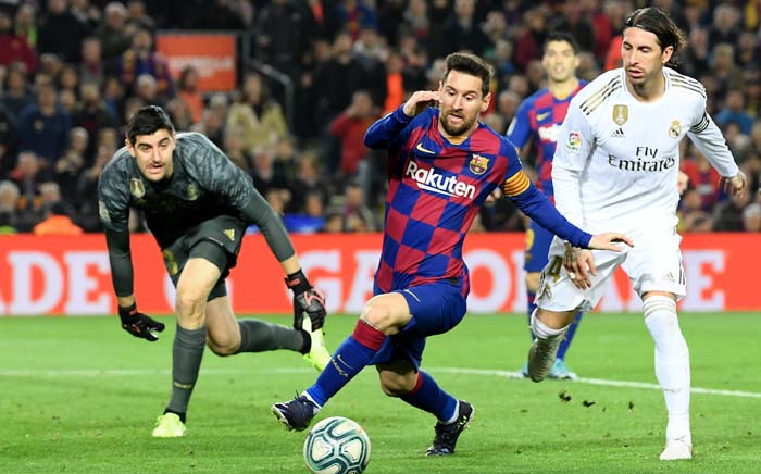 """FILE: Real Madrid's Spanish defender Sergio Ramos (R) challenges Barcelona's Argentine forward Lionel Messi (C) next to Real Madrid's Belgian goalkeeper Thibaut Courtois during the """"El Clasico"""" Spanish League football match between Barcelona FC and Real Madrid CF at the Camp Nou Stadium in Barcelona on 18 December 2019. Picture: AFP."""