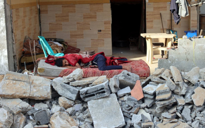 A Palestinian boy sleeps in the ruins of his family house that was destroyed in Israeli air strikes during the most recent Israeli-Palestinian fighting, in Gaza City, on 2 July 2021. Picture: MOHAMMED ABED/AFP
