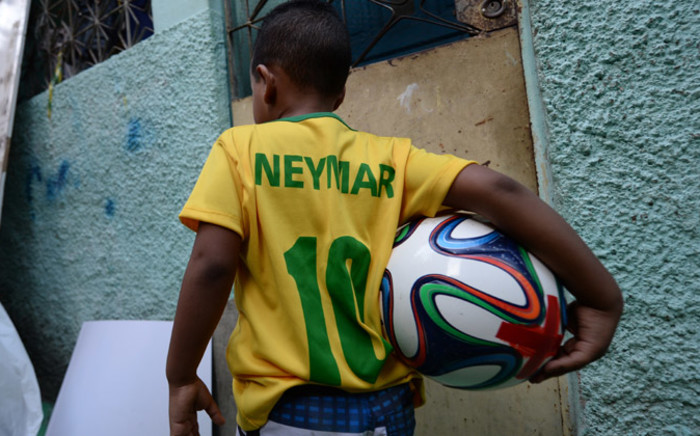 A boy of the Jacarezinho shantytown walks with a football after decorating the streets and houses of the neighborhood for the upcoming Fifa World Cup. Picture: AFP