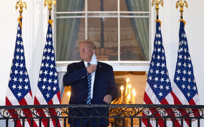 US President Donald Trump removes his mask upon return to the White House from Walter Reed National Military Medical Center on 5 October 2020 in Washington, DC. Trump spent three days hospitalised for coronavirus. Picture: AFP.