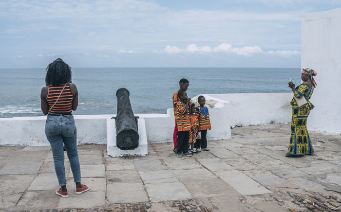 "Tourists pose for pictures at the Cape Coast Castle on 18 August 2019. African-American visitors are flocking to Ghana as it marks the ""Year of Return"" to remember the 400th anniversary of the first slave ship landing in Virginia. Picture: AFP"