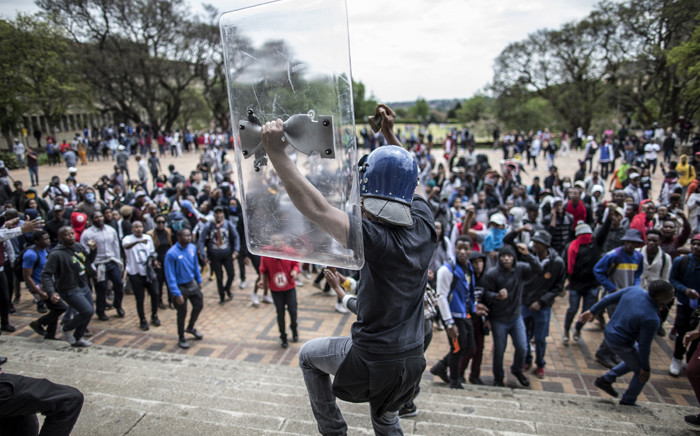 FILE: Former Wits University SRC leader Mcebo Dlamini dances with a helmet belonging to the university private security and with a shield during a running battle with the police forces on campus as he takes part in student protests. Picture: AFP.