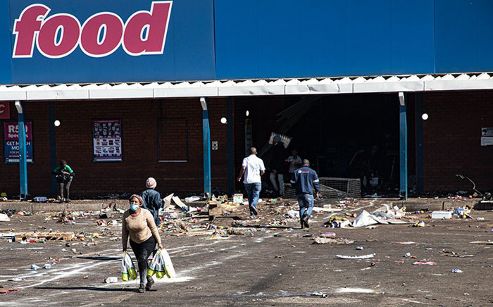 Looters walk off with their loot from a store in Vosloorus on 12 July 2021. Picture: Boikutso Ntsoko/Eyewitness News