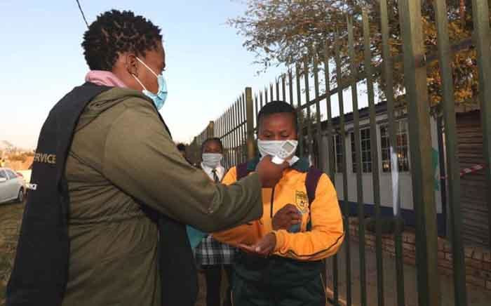 FILE: A teacher takes the temperature and sanitises the hands of a pupil returning to Olivenhoutbosch Secondary School on 8 June 2020. Picture: Gauteng Provincial Government.