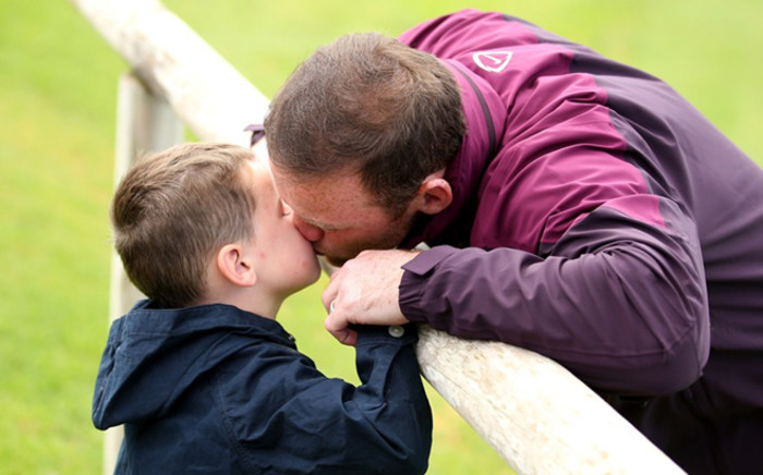 Wayne Rooney kisses his son before practice during the 2014 Fifa World Cup. Picture: AFP.