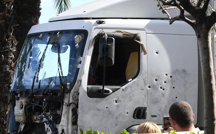 A man takes a pictures as the truck, riddled with bullets, that was driven by a man through a crowd celebrating Bastille Day is towed away by a breakdown lorry in the French Riviera city of Nice on 15 July 2016. Picture: AFP