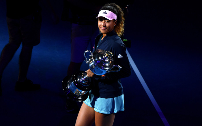 Japan's Naomi Osaka celebrates with the championship trophy during the presentation ceremony after her victory against Czech Republic's Petra Kvitova in the women's singles final on day 13 of the Australian Open. Picture: AFP.