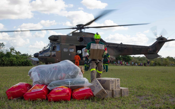 People watch on as food and supplies get dropped in the Estaquinha area. Picture: Christa Eybers/EWN