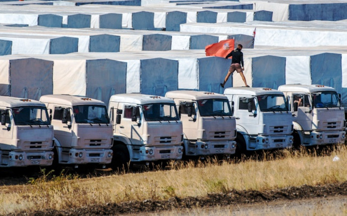 A driver installs a red flag on his lorry, parked with other lorries of the Russian humanitarian convoy not far from a checkpoint at the Ukrainian border some 30 km outside the town of Kamensk-Shakhtinsky in the Rostov region, on 20 August,2014. Picture: AFP.