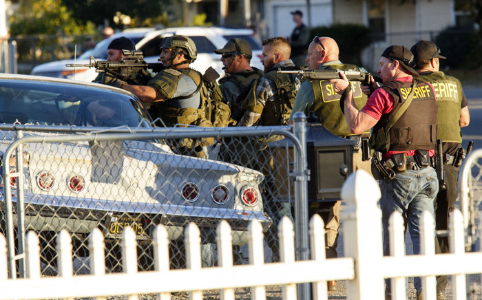 Law enforcement officers search for the suspects of a mass shooting 2 December, 2015 in San Bernardino, California. A man and a woman suspected of carrying out a deadly shooting at a center for the disabled were killed in a shootout with police, while a third person was detained, police said. Picture: AFP.