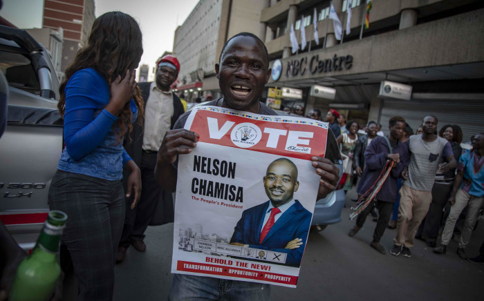 FILE: MDC supporters hold placard with the face of party leader Nelson Chamisa outside the party's headquarters in Harare. Picture: EWN