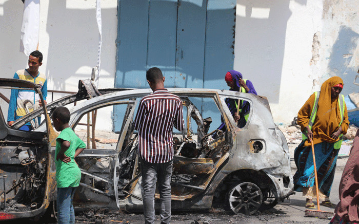 People start cleaning debris at the site where a car bomb exploded near the Somali parliament in Mogadishu, Somalia, on 8 January 2020.  Picture: AFP