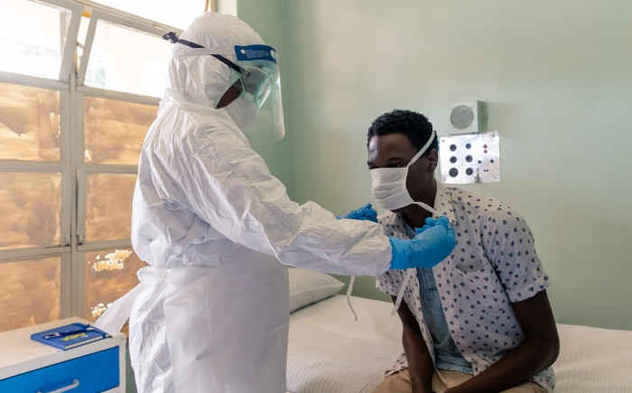 A medical staff member wearing protective equipment places a face mask on a mock patient at the Wilkins Infectious Diseases Hospital in Harare on 11 March 2020. Picture: AFP
