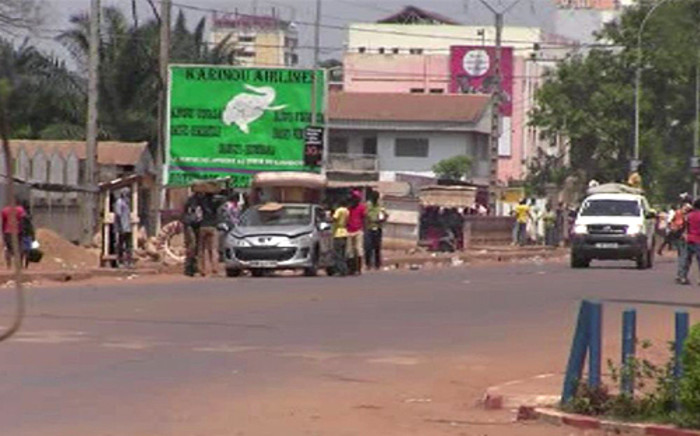 A video grab shows overloaded cars and suspected looters carrying goods in a street in Bangui on March 24, 2013. Looters and armed gangs roamed the streets of the Central African Republic capital after rebels seized control of the city. Picture: AFP