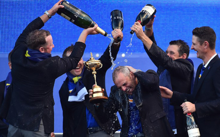 FILE: Team Europe captain Paul McGinley of Ireland is sprayed with champagne as he holds the trophy after his team retained the Ryder Cup on the final day of the Ryder Cup golf tournament. Picture: AFP.