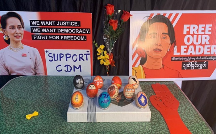 This photo taken and received from an anonymous source via Facebook on April 4, 2021 shows posters featuring detained civilian leader Aung San Suu Kyi and eggs decorated with messages in support of protesters demonstrating against the military coup in Yangon, to coincide with Easter Sunday. Picture: AFP.