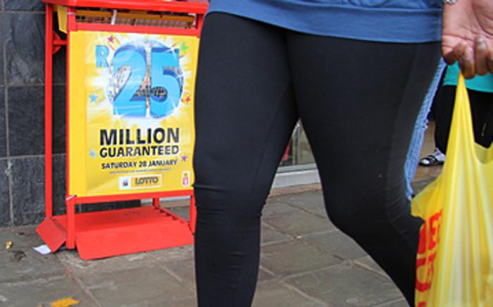 A woman walks past a lotto stand in Pretoria. Picture: EWN