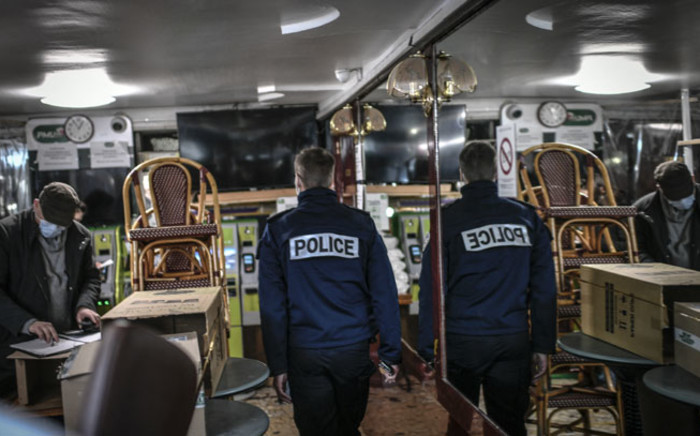 FILE: A French police officer inspects a bar in Paris on 3 February 2021, during a patrol to control the implementation of sanitary measures and restrictions aimed at curbing the spread of the COVID-19 pandemic. Picture: Stephane de Sakutin/AFP