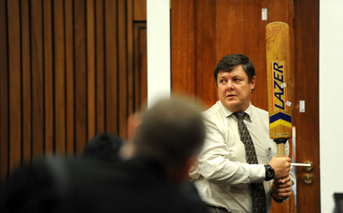 Police forensic expert Colonel Gerhard Vermeulen holds a cricket bat while standing next to the toilet door of murder accused Oscar Pistorius during cross-examination at the High Court in Pretoria on 12 March 2014. Picture: Pool.