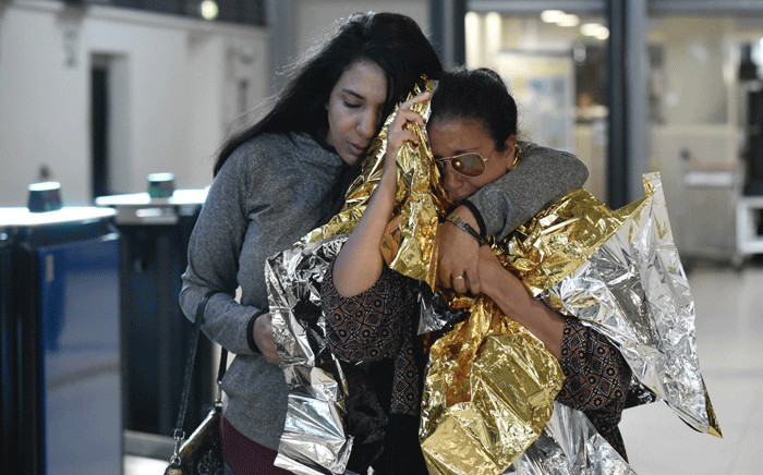 People evacuated from the French Caribbean island of Saint-Martin that was hit by Hurricane Irma react as they walk after landing at the Roissy-Charles de Gaulle airport, north of Paris, on 11 September 2017.  Picture: AFP.