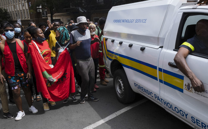 Protesters walk behind a forensic pathology service vehicle carrying the body of a passerby that was shot dead after South African police moved to disperse students protesting against refusal by a top Johannesburg-based university to register those in arrears with tuition fees, in Braamfontein, Johannesburg on 10 March 2021. Picture: Emmanuel Croset/AFP