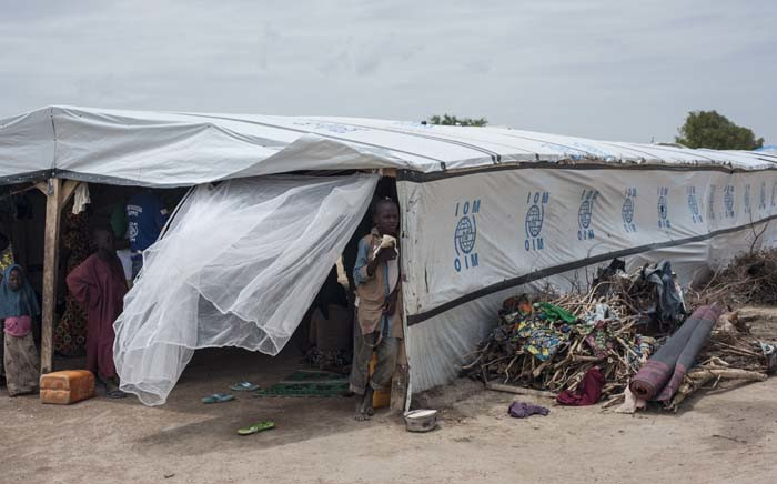 "FILE; Children stand in the shade of a temporary structure in one of the IDP (Internally Displaced People) camps in Pulka on 1 August 2018. As the presidential race heats up ahead of February polls, the Nigerian government and officials of Borno state, the epicentre of the Boko Haram Islamist insurgency, are encouraging and facilitating the ""return"" of tens of thousands of people. Picture: AFP"