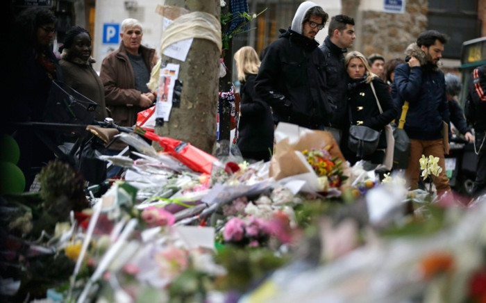 FILE: People spend a moment mourning the dead at the site of the attack at the Cafe Belle Equipe on rue de Charonne three days after the terrorist attacks that left over 130 dead. Picture: AFP.
