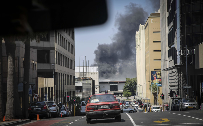Thick clouds of smoke could be seen in the Cape Town CBD as another two trains were alight at Cape Town Station. Picture: Cindy Archillies/EWN