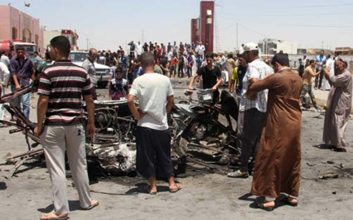 Iraqis inspect the site of a suicide car bomb attack in  the Al-Haq square in Samarra,  a predominantly Sunni town north of Baghdad, on July 5, 2013. Attacks killed five people in town squares in Iraq, including four who died when a suicide bomber set off his vehicle rigged with explosives just before midday prayers. AFP PHOTO/MAHMOUD AL-SAMARRAI