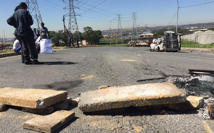 """Hundreds of protesters set alight two vehicles at George Goch hostel in the Joburg CBD during an early morning demonstration. Picture: Vumani Mkhize/EWN."