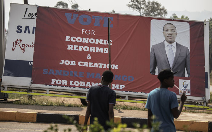 FILE: People walk past eSwatini parliamentary election billboards on 19 September, 2018 in Lobamba. Picture: AFP
