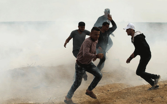 Palestinian protesters run from tear gas fired by Israeli forces during clashes following a protest along the border with Israel, east of Gaza City on April 3, 2018 A Palestinian was shot dead by Israeli forces on the Gaza border, the health ministry in the strip said, as tensions remained days after 17 people were killed when a mass demonstration led to clashes. Picture: AFP.