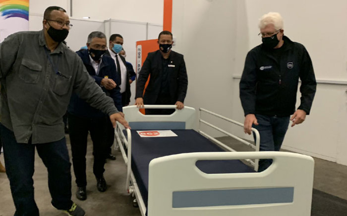 FILE: Western Cape Premier Alan Winde (right) and provincial head of Health Dr Keith Cloete (centre) help officials wheel out a hospital bed as the CTICC's Hospital of Hope is officially decommissioned on 21 August 2020. Picture: Kaylynn Palm/Eyewitness News.