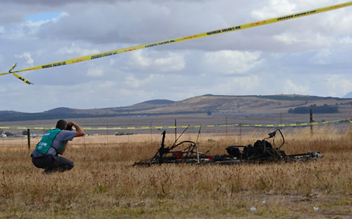 A police crime scene expert kneels next to the wreckage of the microlight that crashed at the Wintervogel airstrip near Malmesbury on 10 January 2013. Picture: Aletta Gardner/EWN