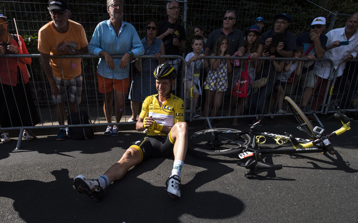 Germanys Tony Martin, wearing the overall leaders yellow jersey, sits on the ground after a fall during the 191.5 km sixth stage of the 102nd edition of the Tour de France cycling race on 9 July 2015, between Abbeville and Le Havre, northern France. Picture: AFP.