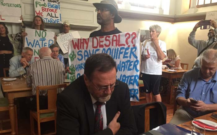 Philippi Horticulture Area Food and Farming campaign's Nazeer Sonday hold a placard behind Environmental Affairs MEC Anton Bredell at the Cape Town Press Club. Picture: Monique Mortlock/EWN.