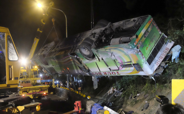 A bus that crashed along a highway is lifted by cranes in Taipei on 14 February, 2017. A bus in Taiwan reported to have been taking local tourists home from visiting seasonal cherry blossoms veered off a highway with 32 feared dead, the national fire department said. Picture: AFP.
