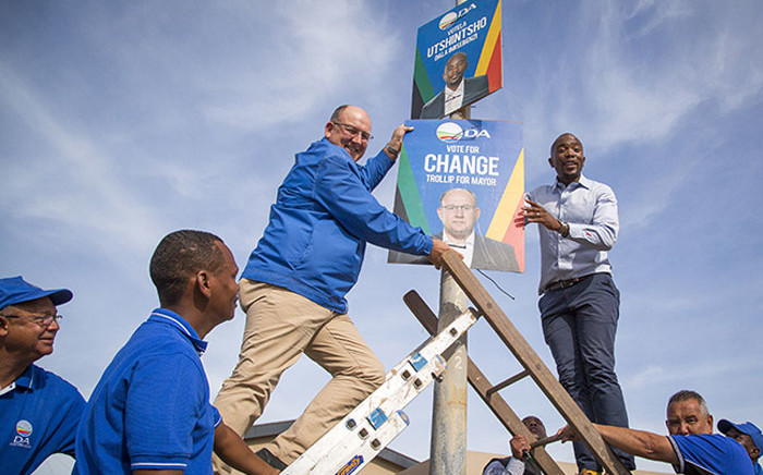 DA leader Mmusi Maimane (R) and Nelson Mandela Bay mayoral candidate Athol Trollip (L) fix a placard to a lamp post in Bethelsdorp, Port Elizabeth, on 24 June 2016. Picture: Aletta Harrison/EWN