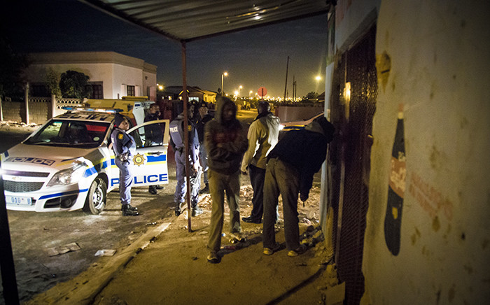 Police and a foreign national inspect his spaza shop in Mamelodi West after it was looted on 21 June 2016. Picture: Thomas Holder/EWN.