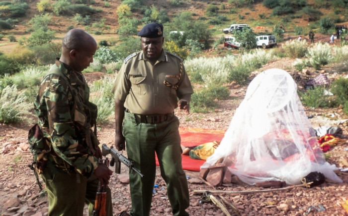 Security officers talk as they stand next to a mosquito net used by a worker who slept there at a quarry near Mandera, northeastern Kenya on 2 December 2014. Picture: EPA.