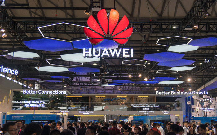 People gather at the Huawei stand during the Mobile World Conference in Shanghai on 27 June 2018. Picture: AFP