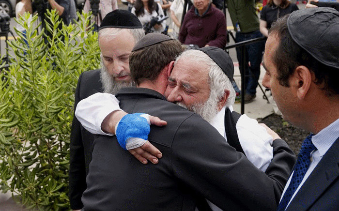 Executive Director Rabbi Yisroel Goldstein (2nd R), who was shot in the hands, hugs his congregants after a press conference outside the Chabad of Poway Synagogue on 28 April, 2019 in Poway, California. Picture: AFP
